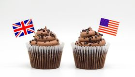 Two chocolate chip swirl cupcakes with tricolor American flag and British Union Jack flag toothpicks in them isolated on white. Two creamy chocolate chip swirl stock image