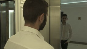 Two creative businessmen greet in the elevator and laugh. HD stock video