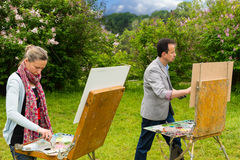 Two creative concentrated artists in a process in a park. Two creative concentrated artists in a process of  working  on a trestle and easel painting with oils Stock Images