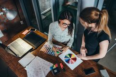 Two creative female designers choosing colors working with colour palette in the office Royalty Free Stock Photography
