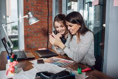 Two creative female designers choosing colors working with colour palette in the office stock photos