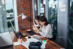 Two creative female designers choosing colors working with colour palette in the office royalty free stock images