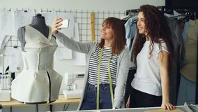 Two creative female designers are making selfie with smart phone while standing beside tailoring dummy in workplace. Two creative female designers are making stock video