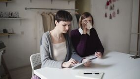 Two creative woman using tablet for new project on background hanging clothes. Two creative woman using tablet for new project. Craft woman using tablet pc for stock footage
