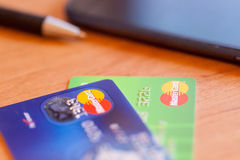 Two credit cards, pen and phone on the table. Soft focus Stock Image