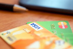Two credit cards, pen and phone on the table. Soft focus Stock Images