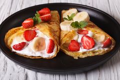 Two crepes with fresh strawberries, bananas and cream Royalty Free Stock Images