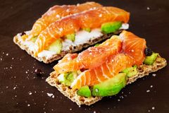 Two Crisp sandwiches with avocado and smoked salmon. Slate background. royalty free stock photos