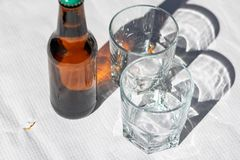 Two cristal glasses and one beer bottle on a white paper tablecloth. Sunny scene with shadows. Concept- share stock photos