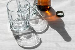 Two cristal glasses and one beer bottle on a white paper tablecloth. Sunny scene with shadows. Concept- share royalty free stock images
