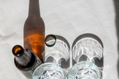 Two cristal glasses and one beer bottle on a white paper tablecloth. Sunny scene with shadows. Concept- share stock photo