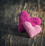Two crochet pink hearts on wooden background Stock Photos