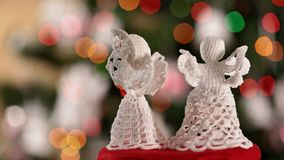 Two xmas angels spinning in front of christmas tree stock footage