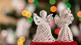 Two crocheted xmas angels decorations on blinking lights background stock footage