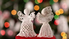 Two crocheted xmas angels spinning in front of christmas tree stock footage
