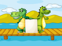 Two crocodiles holding an empty board Royalty Free Stock Image