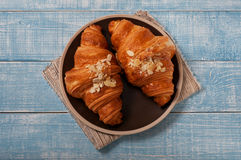 Two croissant with almonds on blue wooden background Stock Images