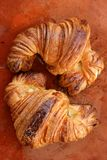 Two croissant pastries over orange clay Royalty Free Stock Image