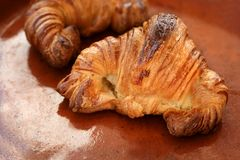 Two croissant pastries over orange clay. Two croissant pastries over orange brown clay background Stock Images