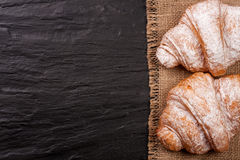 Two croissant sprinkled with powdered sugar on black stone background with copy space for your text. Top view Royalty Free Stock Photo