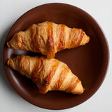 Two croissants on brown plate. Two french croissants on brown plate, from above Royalty Free Stock Photography