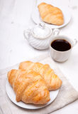 Two croissants with coffee on the white table Stock Photos