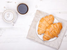 Two croissants with coffee on the white table Royalty Free Stock Image