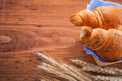 Two croissants and ears of wheat on old wooden Stock Photo