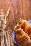 Two croissants and ears of wheat on old wooden Royalty Free Stock Image