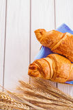 Two croissants and ears of wheat on white painted Royalty Free Stock Photography
