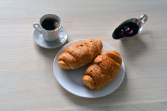 Two croissants on a plate with a cup of coffee and a saucer with Royalty Free Stock Photos