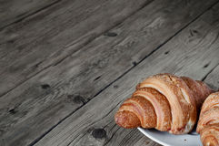 Two croissants on a plate in the foreground on table Stock Photography