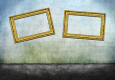 Two crooked golden frames. On gray dirty wall Royalty Free Stock Photo