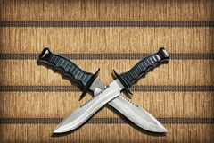 Two Crossed Blades Tactical Combat Hunting Survival Sawback Bowie Knives Set On Yellow Plaited Paper Parchment Place Mat Vignetted Stock Images