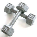 Two crossed dumbells. Two 8 pound dumbells crossed over each other on a white background stock image