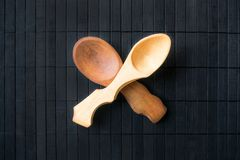 Two crossed empty handmade wooden spoons from different wood and. Different sizes on a black wooden background. Beautiful homemade spoons in a rustic style stock images