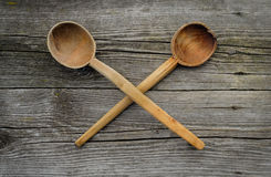 Two crossed old wooden spoons on rustic background Royalty Free Stock Images