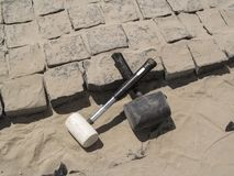 Two crossed rubber hammers lie on the unfinished laying of granite paving stones Royalty Free Stock Images