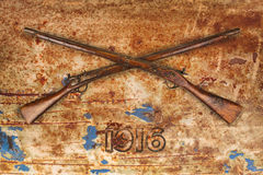 Two crossed vintage wooden rifles against a rusty background Royalty Free Stock Photos