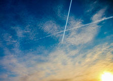 Two crossing airplane traces in bright blue sky during the dawn Royalty Free Stock Images
