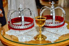 Two crowns and a glass of wine for orthodox wedding stock photos