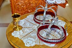 Two crowns and a glass of wine for orthodox wedding stock photography