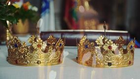 Two crowns for wedding ceremony in the Church. Church attributes for wedding ceremony. Gold crowns are on the altar. Attributes of priest stock video footage