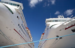 Two Cruise Ships Docked. Two cruise ships, side by side, docked at a pier at a port of call.  Deep blue sky in background offsets brilliant white of ships Stock Photography