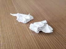 Two crumpled pieces of paper lay on wooden desk table royalty free stock photos