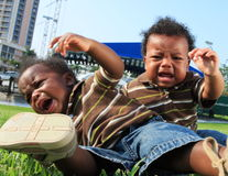 Two Crying Babies. Sitting on the grass and toppling over Stock Photography