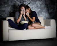Two crying girls looks TV Royalty Free Stock Image
