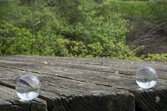 Twin inverted views. Two crystal balls produce inverted views of the landscape while resting on a rough wooden surface of a weathered picnic table royalty free stock photo