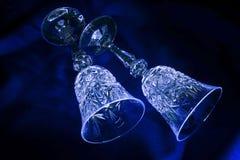 Two crystal glasses on the blue velvet, light brush Stock Photography