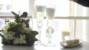Two crystal glasses of champagne and a wedding bouquet. On the table closeup stock footage